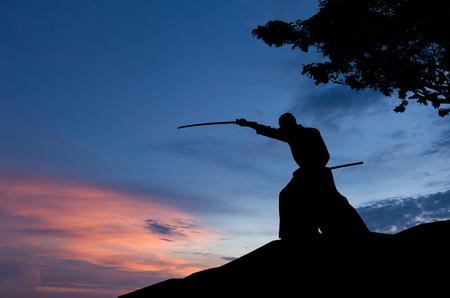 Abstraktes Foto der Mannsilhouette, die Kampfkunst mit Schwert vor Sonnenuntergang zeigt