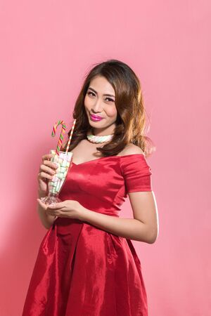 Portrait of young asian woman in red dress posing with sweet candies and marshmallow cocktail in front of pink background 版權商用圖片