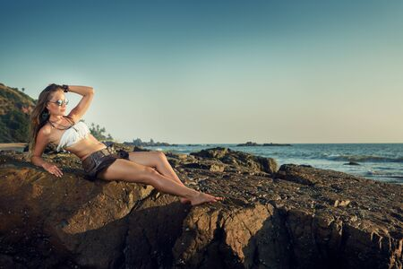 Beautiful young woman sitting on the rock in the beach at sundet and looking at the ocean view.Summer vacations concept of happy travel woman relax on the rock.