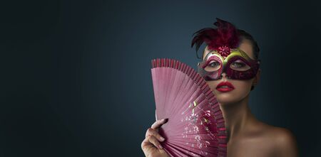 Beauty fashion model woman wearing venetian masquerade carnival mask at party over dark background.