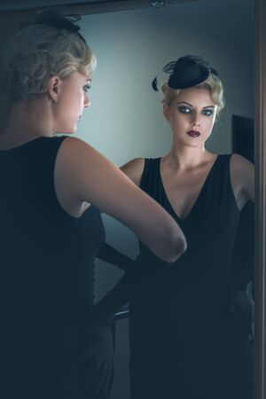 Retro portrait of a beautiful woman next to mirror. Vintage Style