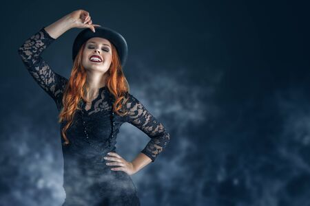 Beautiful woman portrait dressed as witch for Halloween party in witches hat with red hair and bright lips. Posing over dark magic forest background behind. 版權商用圖片