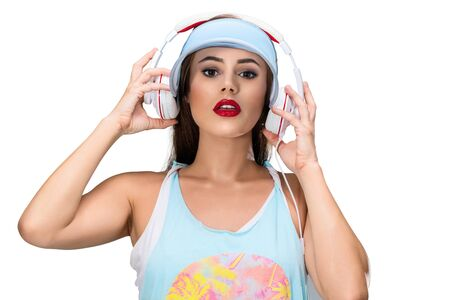 Happy dancing woman listening music with headphones isolated on white background. Studio portrait 版權商用圖片