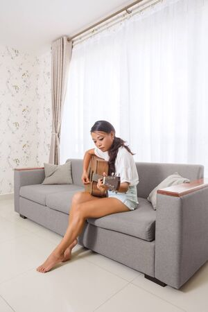 Beautiful asian young woman playing acoustic guitar at home