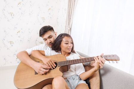 Young asian man teaching his girlfriend to play guitar while both sitting on sofa at home. Young couple enjoying guitar play together
