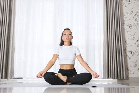 Attractive young asian woman exercising and sitting in yoga lotus position while resting at home