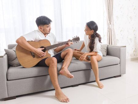 Handsome young asian man playing acoustic guitar and singing for his beautiful girlfriend while sitting on sofa at home.