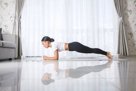 Attractive young asian woman exercising and sitting in yoga position while resting at home 版權商用圖片