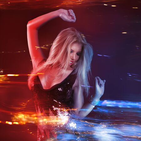 Young blonde woman dancing at night disco club. Motion blur with neon light effect 版權商用圖片