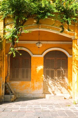 Entrance door and window of vintage house. Detail of ancient building in Hoi An, Vietnam