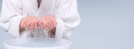 Young woman washing face and hands with clean water