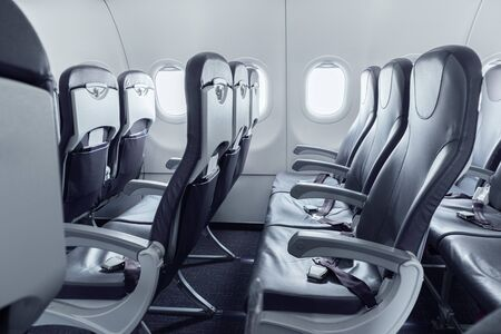 Empty landed passenger airplane cabin during coronavirus outbreak. Global pandemic stopped all travel destinations between countries. Airliner interior without passengers. 版權商用圖片 - 143608287