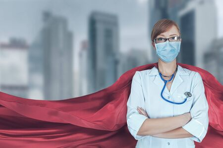 Concept of medical doctors fighting against global pandemic virus. Portrait of young hero woman with super person red cape and medical uniform and mask protect city from corona virus outbreak. 版權商用圖片 - 144576196