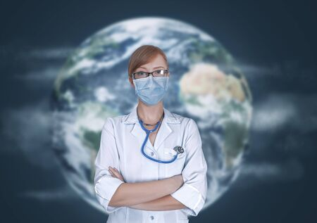 Concept of medical doctors fighting against global pandemic virus. Portrait of young woman in medical uniform and mask protect world from corona virus outbreak in front of Earth globe.