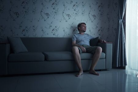 Alone bored Man sitting on sofa at Quarantine. Stay at home. 版權商用圖片 - 145765478