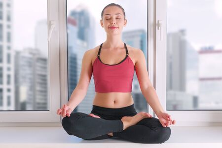 Young woman doing yoga meditation at home in fromt of window