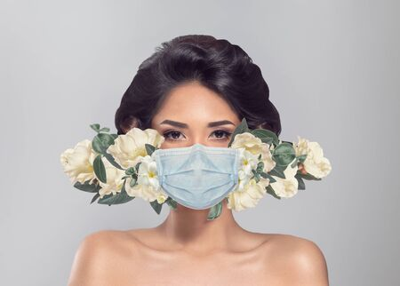 Abstract fashion portrait of woman in protective medical mask with flowers 版權商用圖片