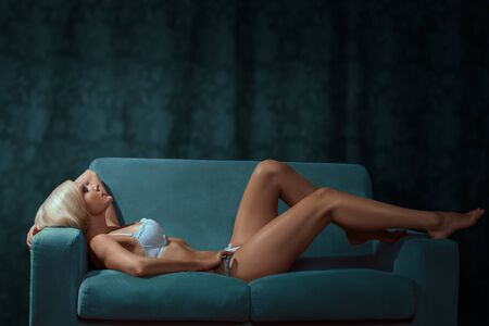 Indoor portrait of young sexy woman relaxing on the sofa