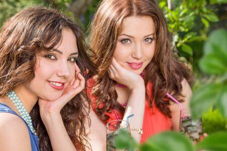 Two young women enjoy drink at backyard garden. Friends meeting outdoors 版權商用圖片 - 149151638