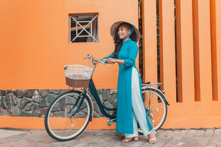 Young woman in traditional vietnamese dress with bicycle walking on street 版權商用圖片