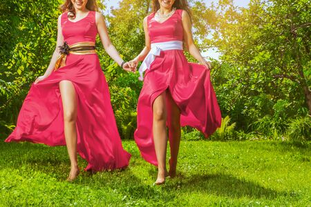 Two happy bridesmaids in red dress running together in garden