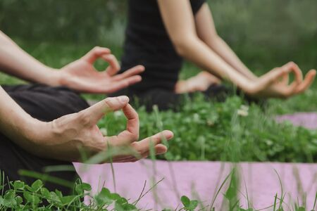 Man and woman doing yoga in lotus position sitting on grass 版權商用圖片 - 150071074