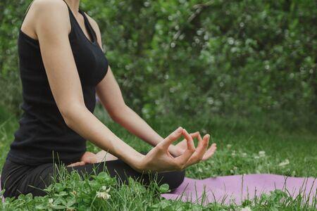 Woman doing yoga in lotus position sitting on grass 版權商用圖片 - 150071077