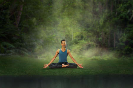 Young man meditation in Lotus position at tropical forest. Man doing yoga training 版權商用圖片 - 151466300