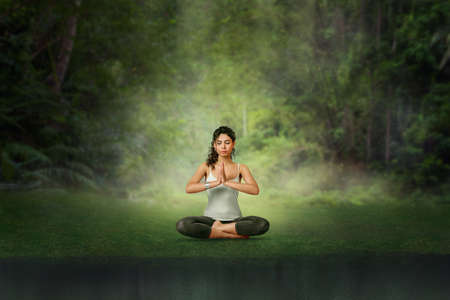 Young woman meditation in Lotus position at tropical forest. Woman doing yoga training 版權商用圖片