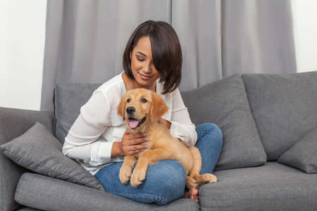 Woman sitting together with her young dog on sofa at home