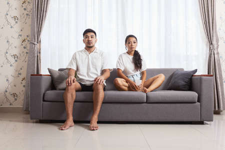 Sad bored couple sitting on sofa at home. Concept of Stay at home during quarantine of covid-19 pandemy 版權商用圖片