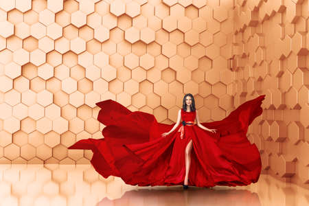 Beautiful young woman posing in long fluttering red dress in abstract interior