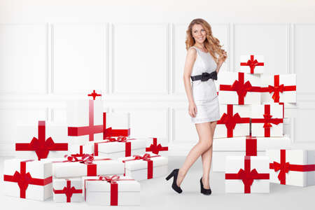 Sale concept with young woman with many gift boxes