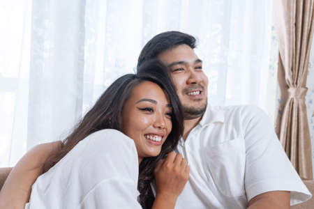 Young happy asian couple relaxing together at home