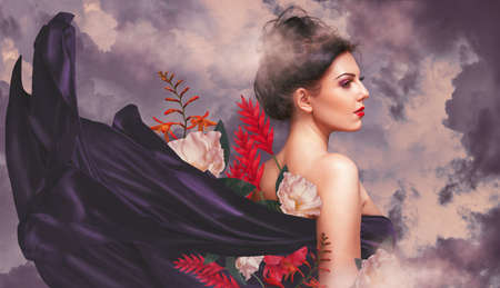 Fantasy portrait of young beautiful woman with silk and flowers