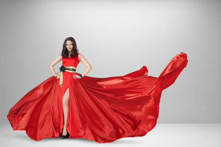 Young beautiful blonde woman in luxury long red silk dress