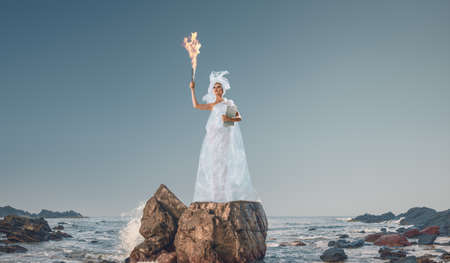 Abstract design of young woman holding torch in her hand in front of sea 版權商用圖片