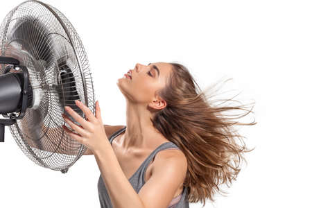 Young woman cooling down with electric fan in hot summer isolated on white background