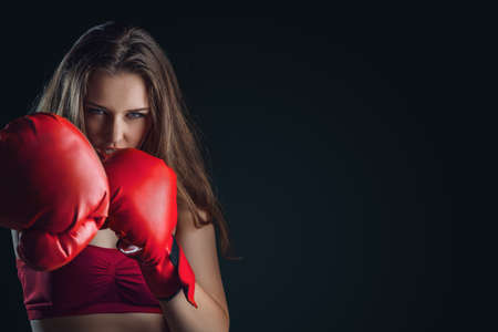 Young woman with boxing gloves isolated on dark background