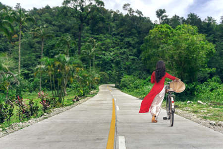 Beautiful young woman in traditional Vietnamese dress Ao Dai walking by the road at jungle forest with bicycle