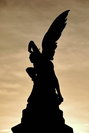 Backlit silhouette of a statue of the fallen angel at sunset