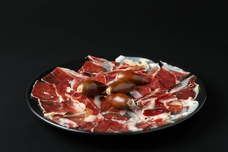 Ration of acorn-fed Iberian ham on a black plate with acorns garnishing. The background is black and the image has selective focus