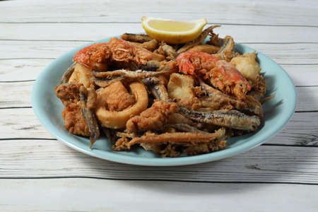 Ration of fried fish (squid, cod, anchovies, baby chopitos and bienmesabe) on wooden table