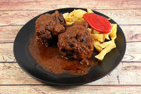 Portion of bullfighting oxtail stewed with a garnish of French fries and red pepper 写真素材