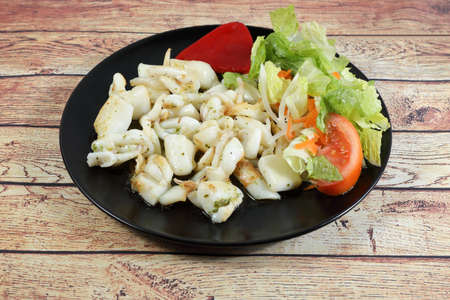 Portion of grilled cuttlefish garnished with lettuce and red pepper, on wooden table 写真素材