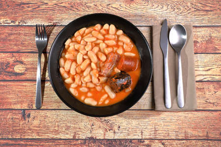 Asturian fabada (white beans) on black plate with napkin and cutlery on rustic wooden table