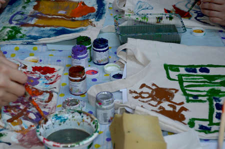 them: Kids are painting and elders help them