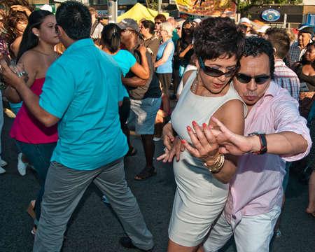トロント, オンタリオ, カナダ - 2012 年 7 月 7 日: 熟女カップル官能的感情的にセント ・ クレア通り回サルサ祭のサルサダンスを踊りながら手を繋い