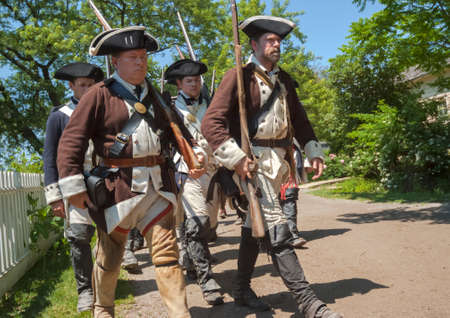 haircut: TORONTO, ONTARIO - JUNE 21, 2009: Group of soldiers armed  with rifles and dressed in old fashion military uniform of 1860s marches at Black Creek Pioneer Village Museum. Vintage style is in effect.