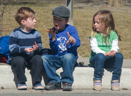 sidewalk talk: TORONTO, ONTARIO, CANADA - APRIL 2, 2011: A group of unidentified children sits along the road and shows different attitude towards the current moment of communication.